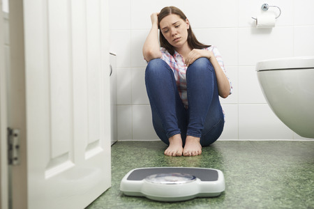 woman sitting on floor: Unhappy Teenage Girl Sitting On Floor Looking At Bathroom Scales