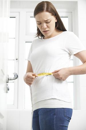 woman measuring waist: Unhappy Teenage Girl Measuring Waist Stock Photo
