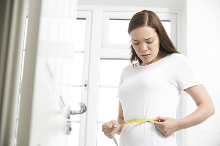 measuring waist: Unhappy Teenage Girl Measuring Waist Stock Photo