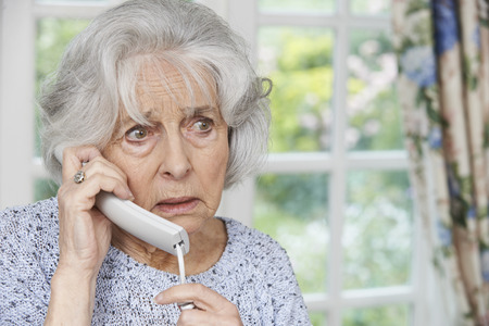 answering call: Worried Senior Woman Answering Telephone At Home