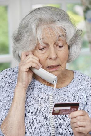 Hogere vrouw die Credit Card Details Op De Telefoon Stockfoto