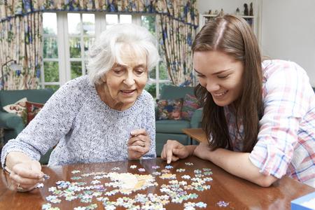 personas sentadas: Adolescente nieta Abuela de ayuda con Jigsaw Puzzle
