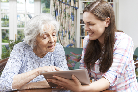 old people: Teenage Granddaughter Showing Grandmother How To Use Digital Tablet
