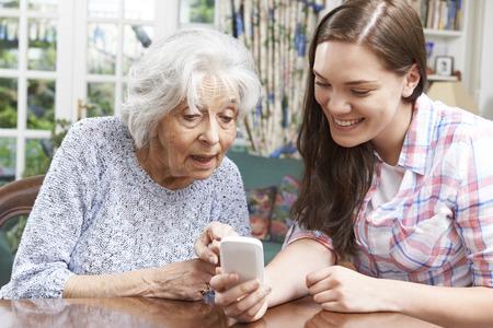personas ayudando: Adolescente Nieta Mostrando Abuela Cómo utilizar el teléfono móvil