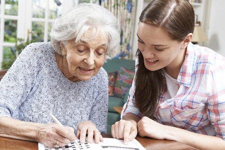 Teenage Granddaughter Helping Grandmother With Crossword Puzzle Banque d'images
