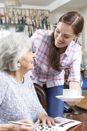 retirement community: Teenage Grandmother Bringing Grandmother Hot Drink Stock Photo