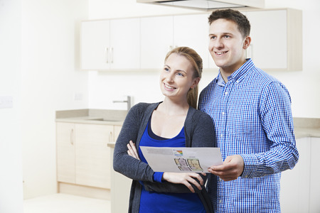 property ladder: Happy Couple Looking At Details For Property They Hope To Buy