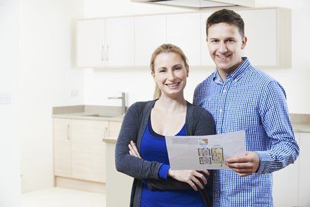 property ladder: Happy Young Couple Sitting On Floor In New Home Stock Photo