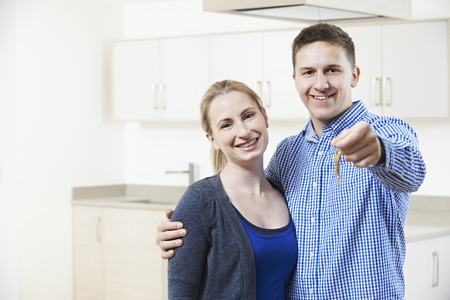 property ladder: Happy Young Couple Holding Keys To New Home
