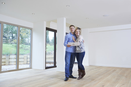 property ladder: Happy Young Couple Looking At Details Of New Home Stock Photo