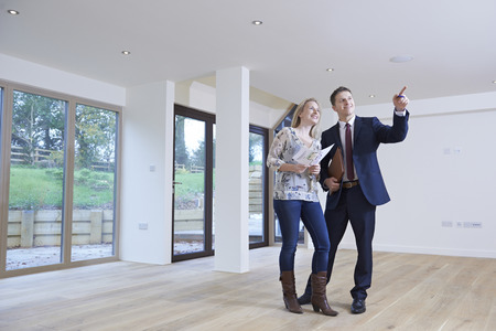 Realtor: Estate Agent Showing Prospective Female Buyer Around Property