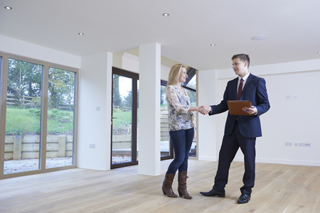 first home: Woman Shaking Hands With Estate Agent In New Home Stock Photo