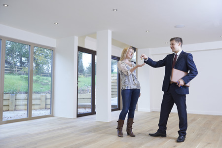property ladder: Woman Collecting Keys To New Home From Estate Agent Stock Photo