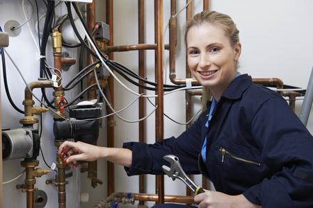 セントラル暖房ボイラーに取り組んでいる女性の配管工 写真素材
