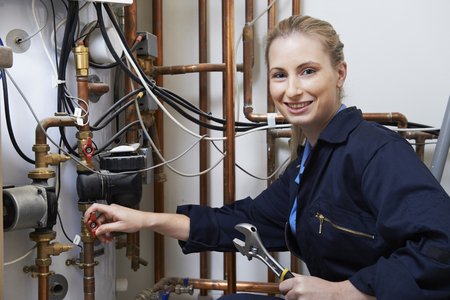 boiler house: Female Plumber Working On Central Heating Boiler
