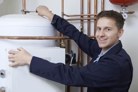 boiler: Portrait Of Male Plumber Working On Central Heating Boiler