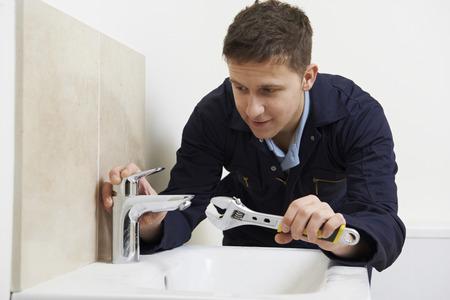 fontanero: Hombre Fontanero que trabaja en fregadero que usa la llave