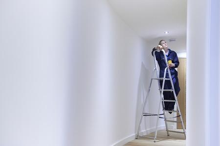 escaleras: Electricista Mujer Instalación de luces en el techo Foto de archivo