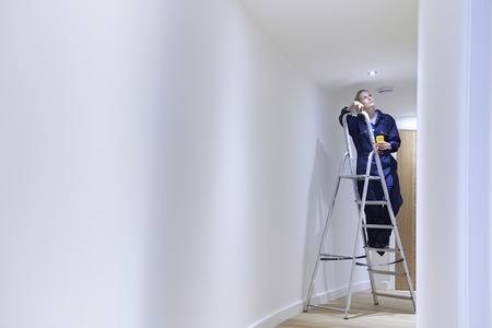 install: Female Electrician Installing Lights In Ceiling Stock Photo