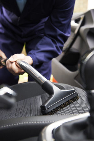 Man Hoovering Seat Van Auto Tijdens Car Cleaning Stockfoto