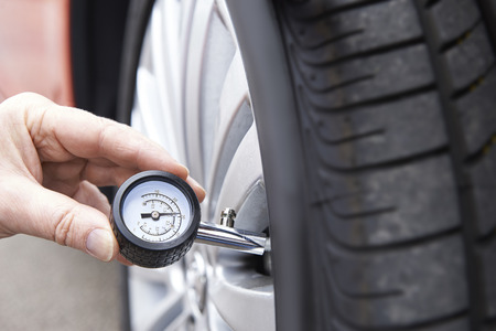 Close-Up Of Man Checking Car Tyre Pressure With Gauge Archivio Fotografico