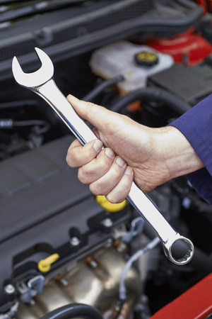 close up  wrench: Mechanic Holding Spanner Fixing Car Engine