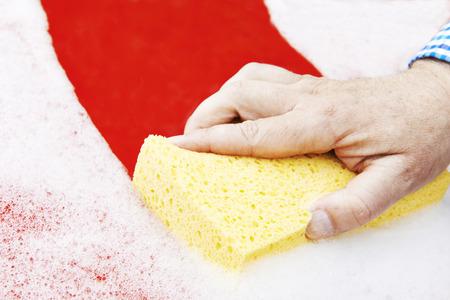 washing car: Close Up Of Hand Washing Car Hood Using Sponge