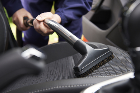 Man Hoovering Seat Van Auto Tijdens Car Cleaning Stockfoto