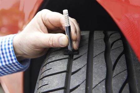 tiefe: Close-Up Of Man Überprüfen Tread On Auto-Reifen mit Manometer Lizenzfreie Bilder