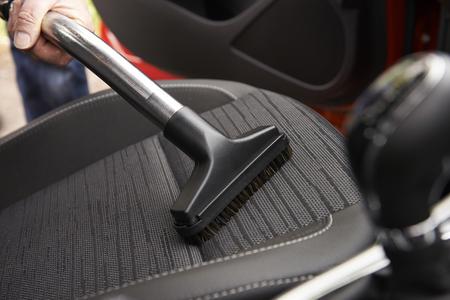 asiento coche: Hombre Hoovering Asiento De Coche Durante Limpieza del Coche Foto de archivo