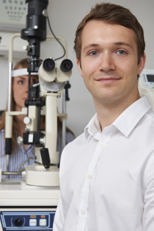 optician: Male Optician Giving Female Patient Eye Examination Stock Photo