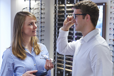 man with glasses: Optician Advising Client On Choice Of Glasses Stock Photo