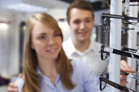 eye exam: Couple Choosing Glasses In Opticians Stock Photo