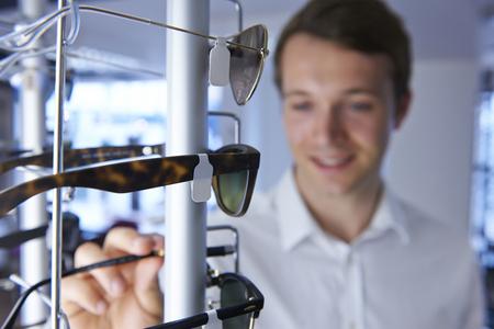 sunglasses: Man Choosing Sunglasses In Shop