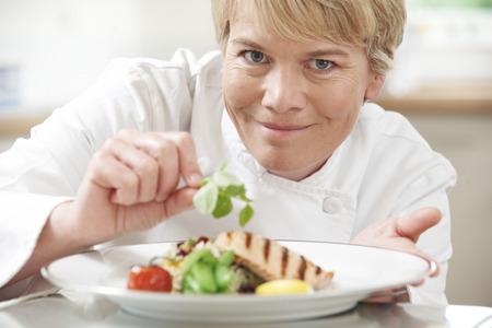 garnish: Chef Adding Garnish To Meal In Restaurant Kitchen