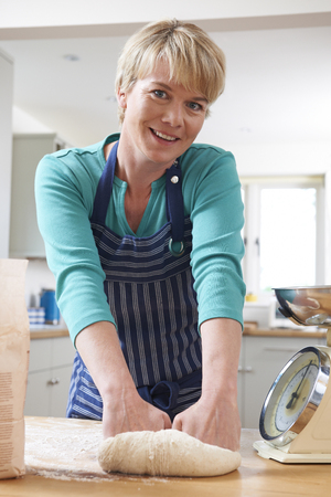kneading: Woman Wearing Apron And Kneading Dough In Kitchen