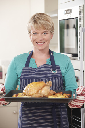 pollos asados: Woman In Kitchen Holding Tray With Roast Chicken