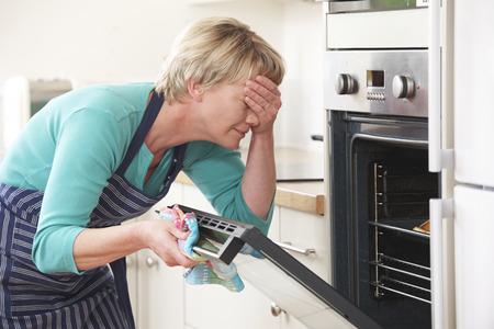 女性のオーブンで探していると、目を覆う悲惨な食事 写真素材