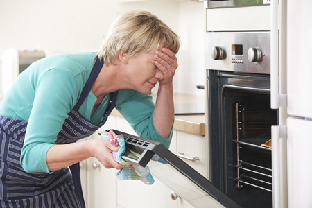 Vrouw die in een oven en voor de ogen dan Disasterous Maaltijd