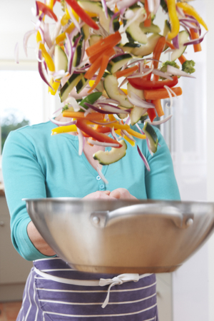 tossing: Female Cook Tossing Vegetables In Pan Obscuring Her Face Stock Photo