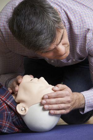 airway: Man In First Aid Class Checking Airway On CPR Dummy