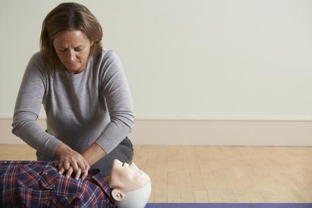 primeros auxilios: Mujer que usa el RCP Técnica En Maniquí En la primera clase de la ayuda