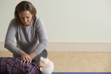 safety first: Woman Using CPR Technique On Dummy In First Aid Class Stock Photo