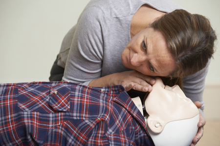 airway: Woman In First Aid Class Checking Airway On CPR Dummy Stock Photo