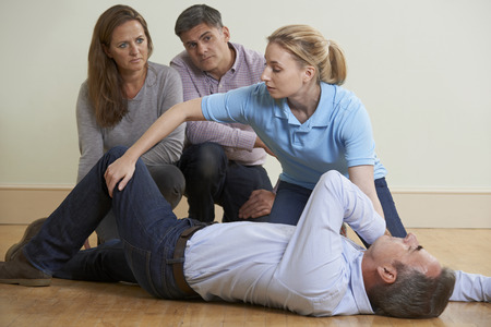 positions: Woman Demonstrating Recovery Position In First Aid Training Class