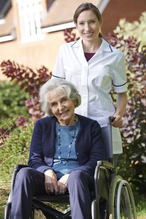 paraplegico: Portrait Of Carer Pushing Senior Woman In Wheelchair Foto de archivo