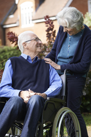 elderly woman: Senior Man In Wheelchair Being Pushed By Wife