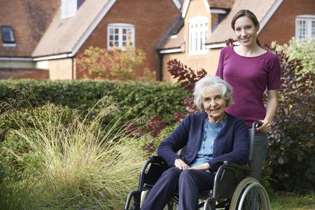 apoyo familiar: Hija Empujar senior madre en silla de ruedas