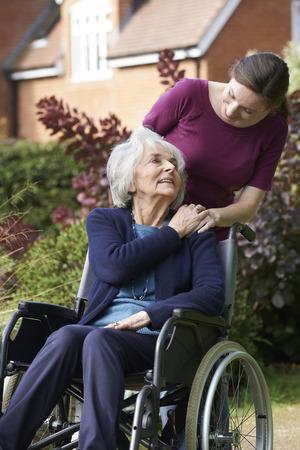 personas sentadas: Hija Empujar senior madre en silla de ruedas
