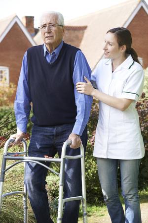 80s adult: Carer Helping Senior Man To Walk In Garden Using Walking Frame